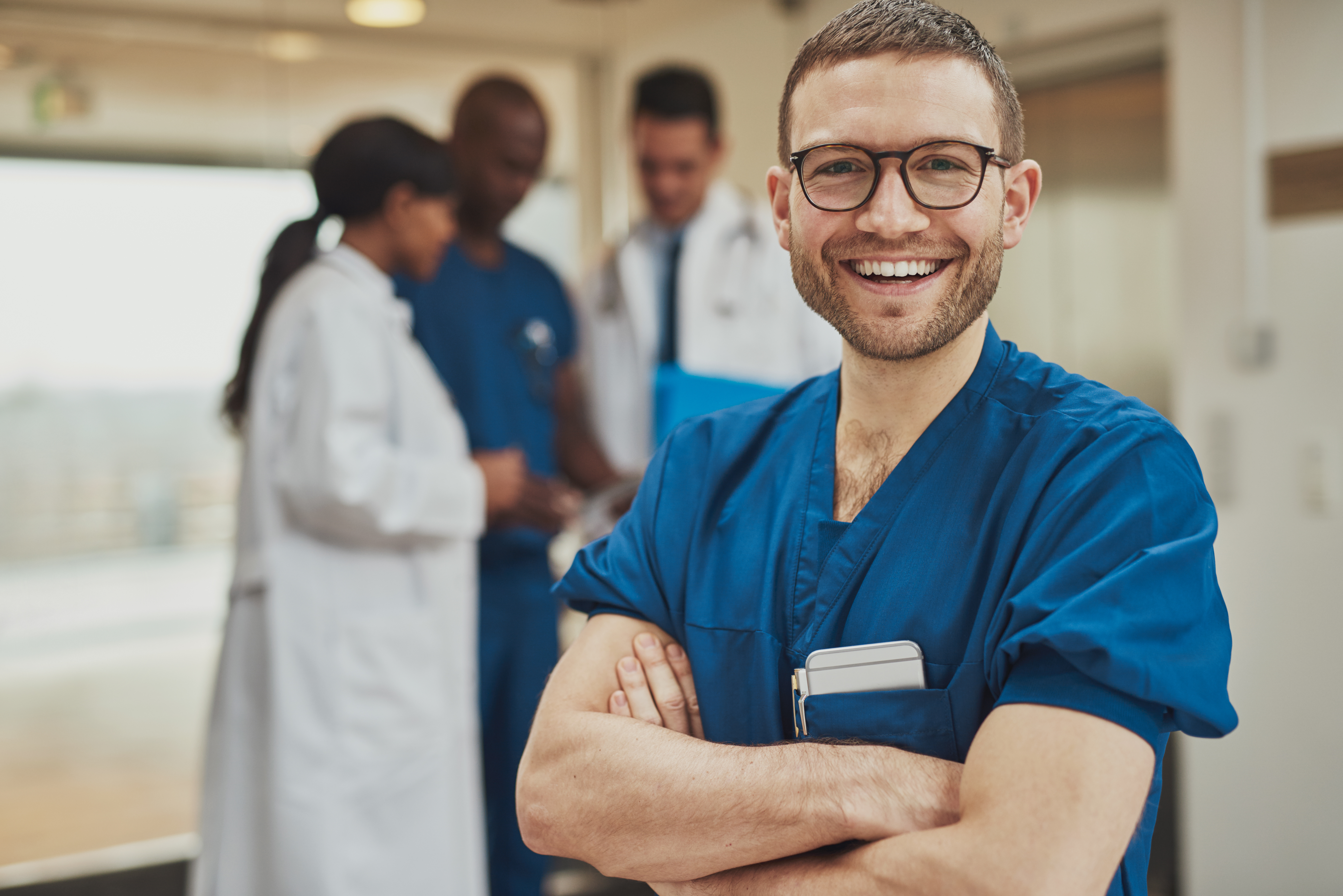 Male nurse standing in front of blurred group of people
