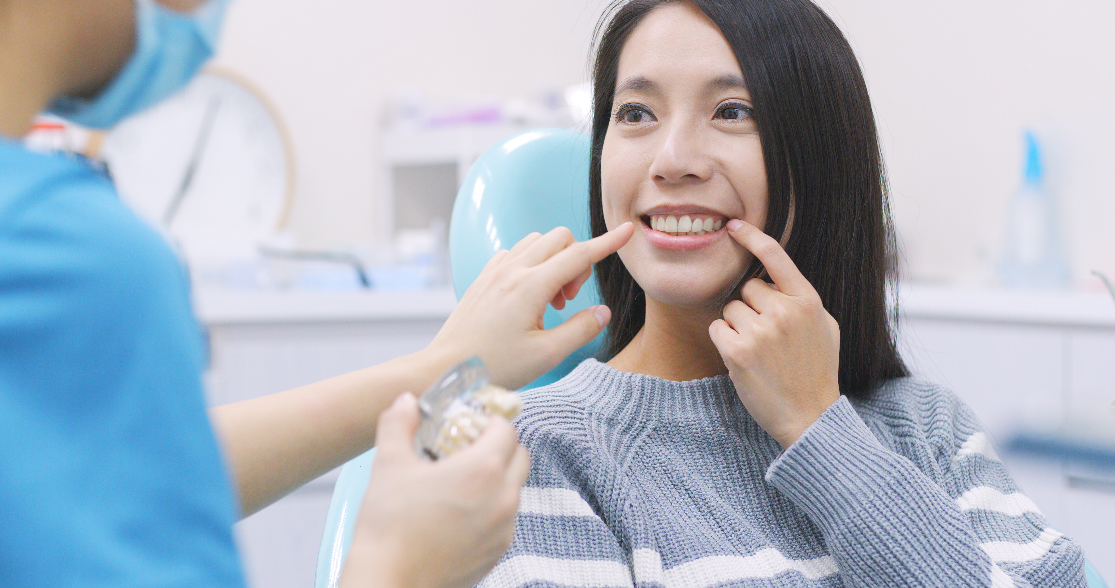 Woman sitting in chair talking to dentist
