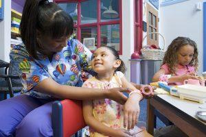 Nurse applying bandage to girls arm. Girl with bandaged arm at table.