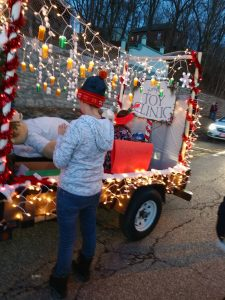 Person standing in front of holiday wagon at parade